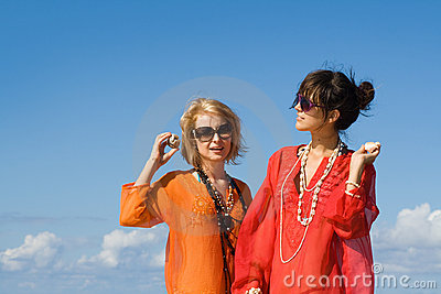 Two beautiful women hearing shells