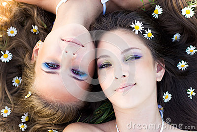 Two beautiful women lying head to head