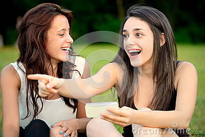 Two beautiful young amazed women pointing outside