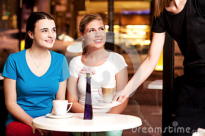 Two beautiful young girls at coffee shop