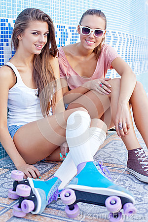 Two beautiful young girls on the floor of an empty pool