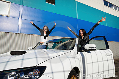 Two beautiful young woman and white sports car