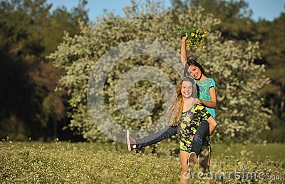 Two beautiful young women piggy-backing in meadow