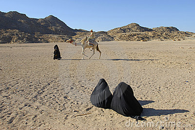 Two bedouin women watching camel ride