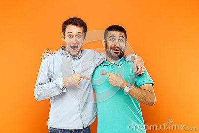 Two best friends hugging, pointing finger each other and looking Stock Photo