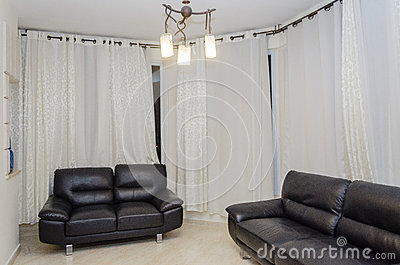 Two Black Couch Against White Curtains In The Cabin Apartments ...