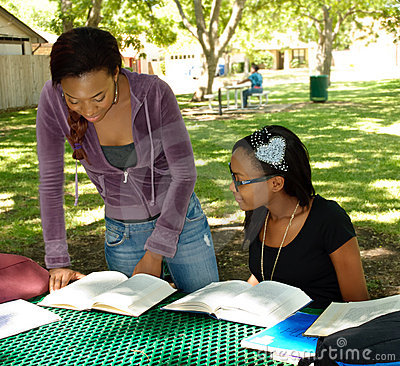 Two black teens study their books at the park