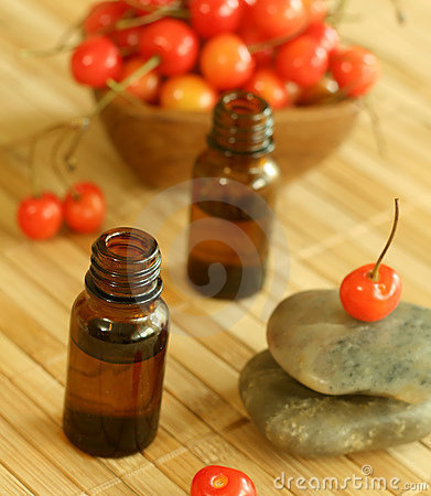 Two bottles of essence oil, stones and fresh cher