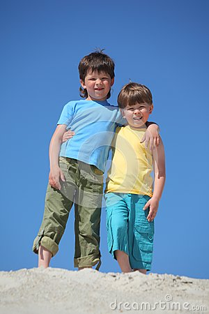 Two boys embrace each other on sand