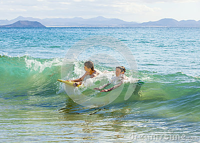 Two boys have fun in the ocean with their boogie boards