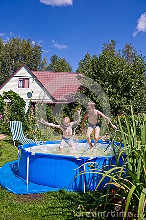 Two boys jumping and splashing in swimming pool