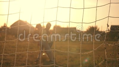 Two boys playing soccer at sunset. A soccer ball is hitting. Football goal. Children`s dreams of victories. Two boys playing soccer at sunset. A soccer ball is stock video footage