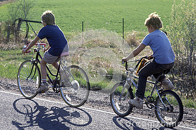 Two boys riding bicycles on rural road, Editorial Stock Photo