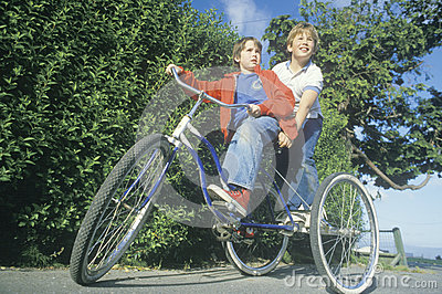 Two boys riding a three wheeled bicycle Editorial Stock Photo