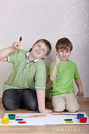 Two boys sit on floor and show their forefingers