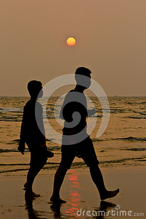 Two boys walking in sunset