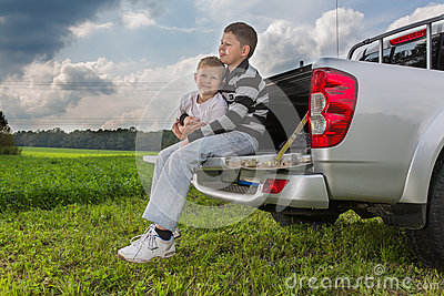 Two brothers siiting on a car trunk on natural Stock Photo