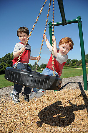 Two brothers on a tire swing