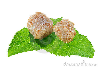 Two brown lump cane sugar cubes over peppermint
