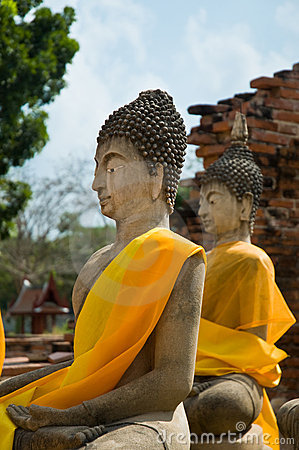 Two Buddha statues with orange scarf
