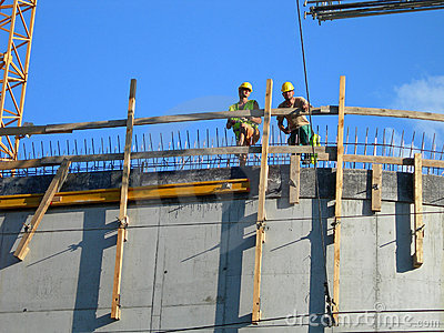 Two builders. Workers on top of a constructed building