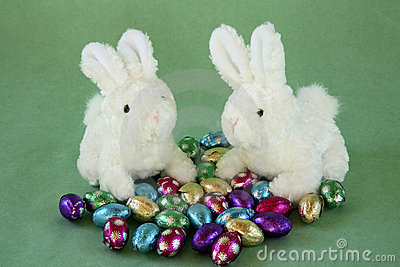 Two bunnies with miniature chocolate eggs.