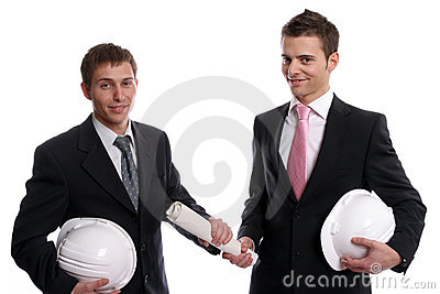 Two business man with safety hats, exchanging a ne