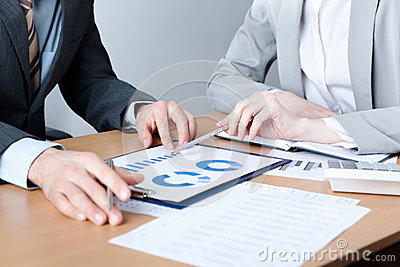 Two business people discuss meeting targets