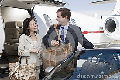 Two Business People Getting In Car