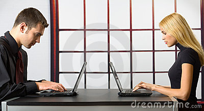 Two business people on laptops