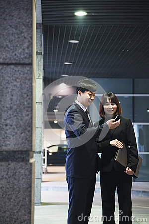 Two business people looking at phone in a parking garage, Beijing