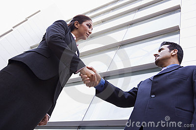 Two business people shaking hands outside office