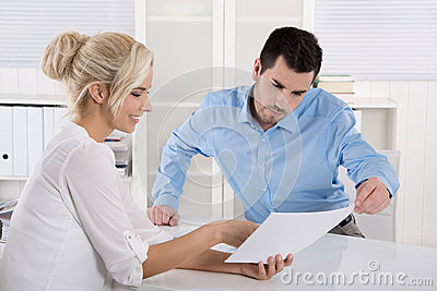 Two business people sitting in the office working in a team look