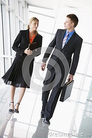 Two business people walking in corridor talking