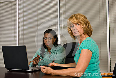 Two business woman working on a laptop computer