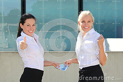 Two business women thumbs up with euro banknotes