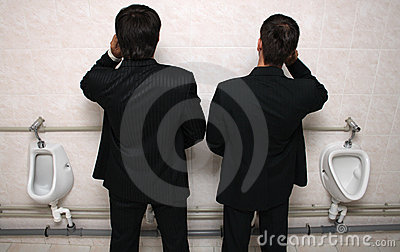 Two businessman with mobile phones in a WC