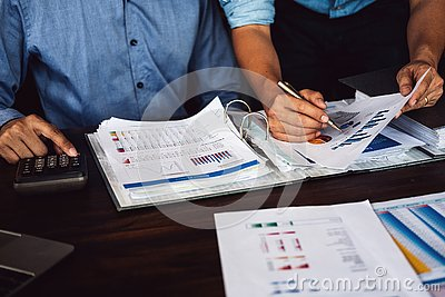 Two businessman planning strategy on desk with paperwork, Strategist team analyze data or information Stock Photo