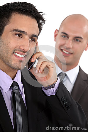 Two businessman receiving a call