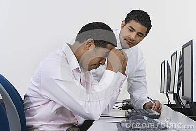 Two Businessmen At Desk In Front Of Computer