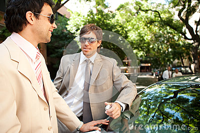 Businessmen meeting around car.