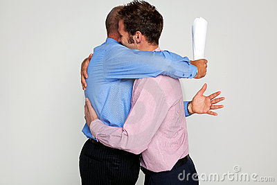Two businessmen hugging