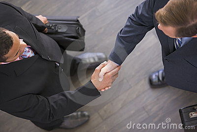 Two businessmen indoors shaking hands