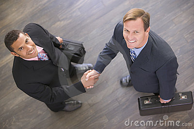 Two businessmen indoors shaking hands smiling