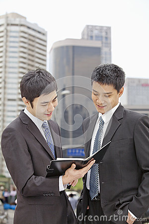 Two Businessmen Looking at Note Pad