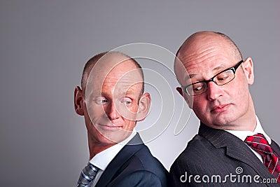 Two businessmen looking over shoulder