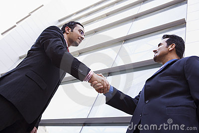 Two businessmen meeting outside office building