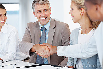 Two businessmen shaking hands in a meeting