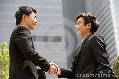 Two Businessmen Shaking Hands Outside Office