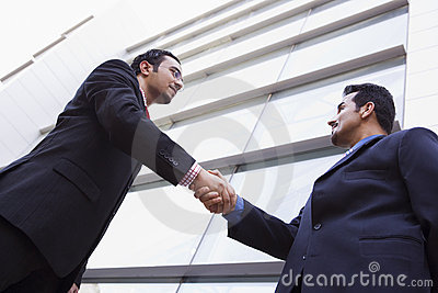 Two businessmen shaking hands outside office build